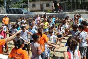 Crianças brincan com os voluntários, numa linda manhã ensolarada